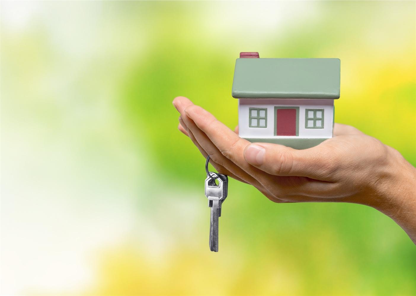 Haus verkaufen und kaufen im Grünen mit Schlüssel und Haus auf der Hand